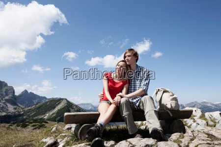 couple sitting on bench on hilltop