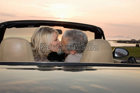 couple kissing in convertible at sunset