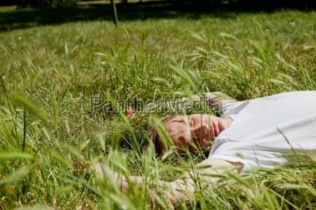 teenage boy laying in tall grass