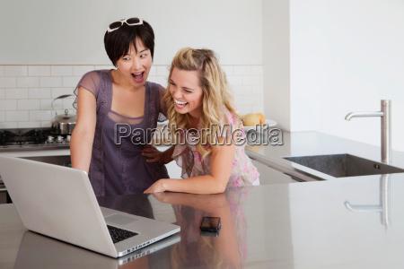 laughing women using laptop in kitchen