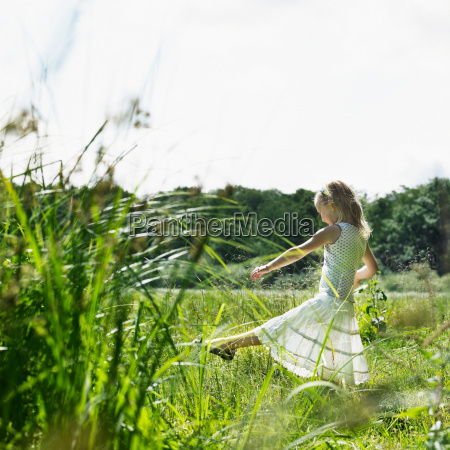 girl playing in tall grass in
