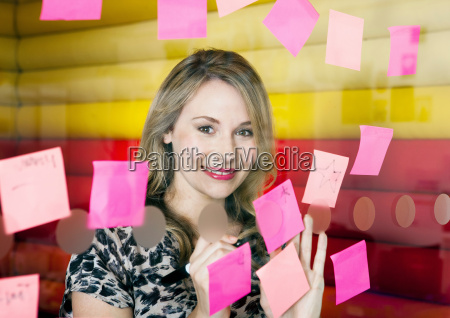 businesswoman sticking notes on window