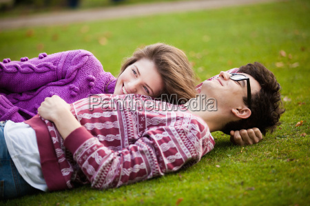teenage couple laying in grass in