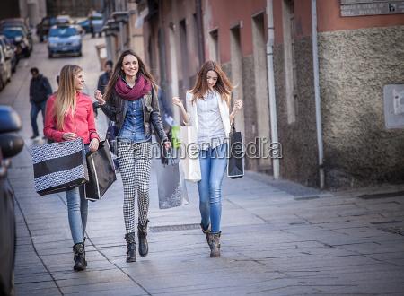 three female friends strolling along street