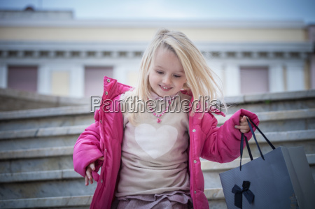 young girl on stairway carrying shopping