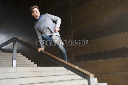 young man carrying digital tablet jumping