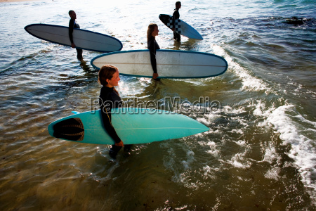 four people standing with surfboards