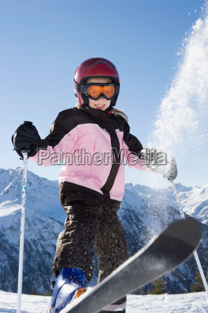 young girl flicking snow off her