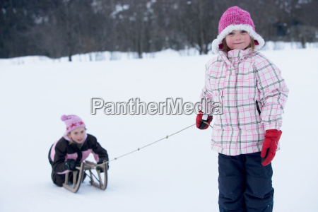 young girls playing with sledge