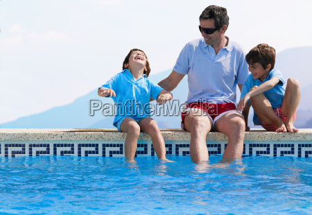 father sitting by swimming pool