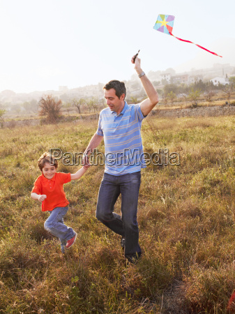 father and son running in field