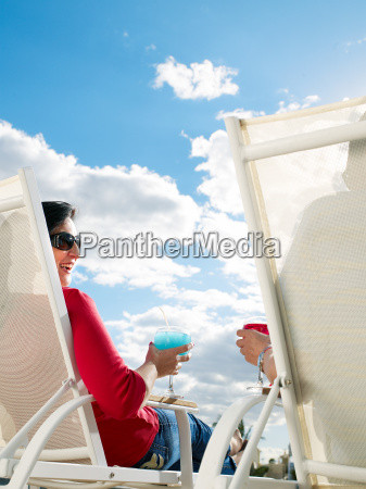 couple relaxing in deckchairs rear view
