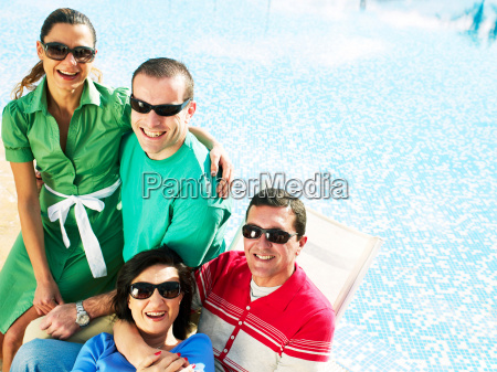 two couples sitting by swimming pool