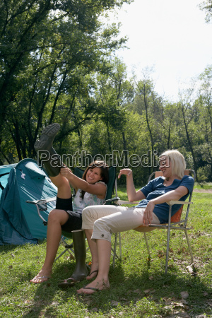 two women sitting at campsite laughing