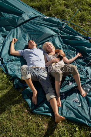 couple lying on unraised tent smiling