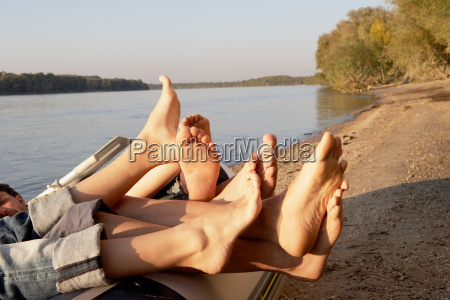four peoples legs hanging over the