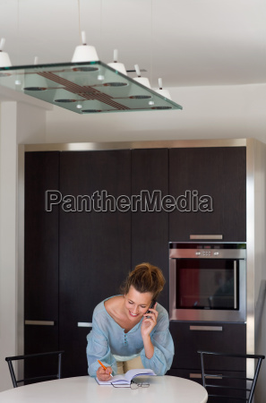 woman in kitchen talking on phone