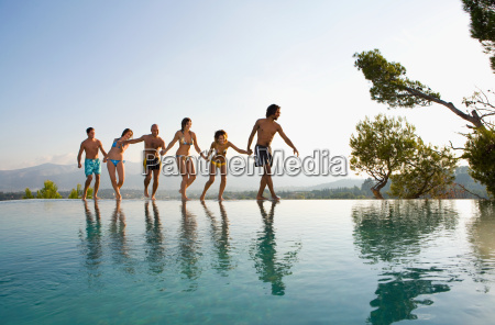 people walking by a pool holding