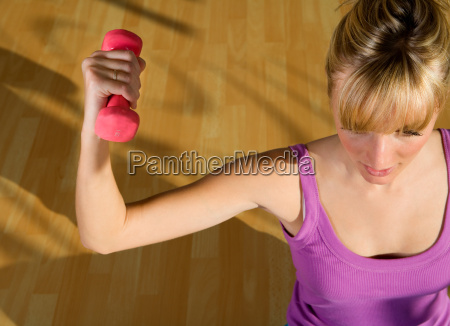 young woman lifting weights in a