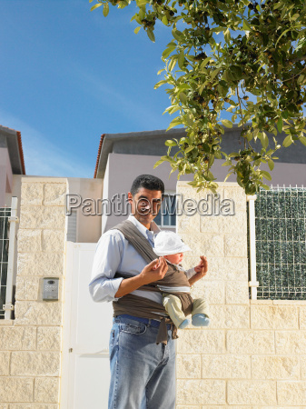 father looking at camera with baby