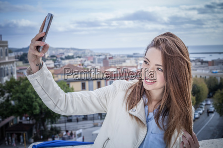 young woman on rooftop taking smartphone