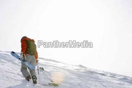 man walking up slope carrying broken