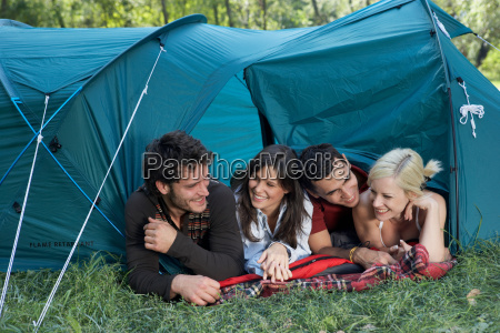 four people lying in a tent
