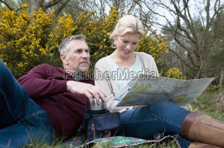 hiking couple picnicing and reading map