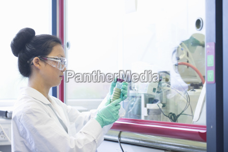 young female scientist looking at