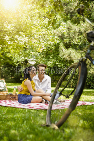 young couple sitting together on picnic