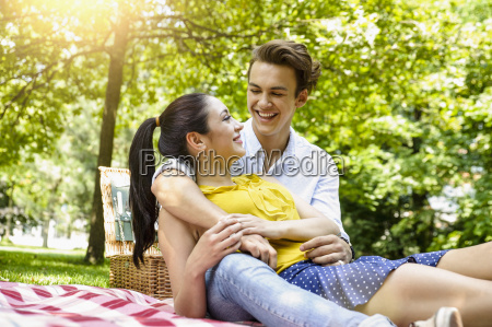young couple snuggling together on picnic