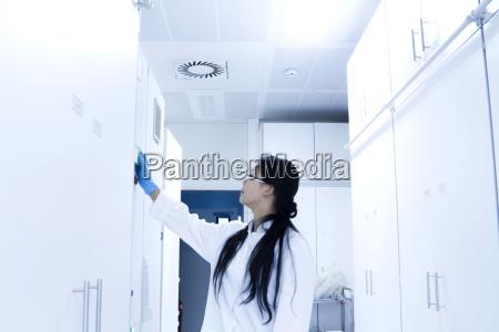 female scientist opening sample cupboard in