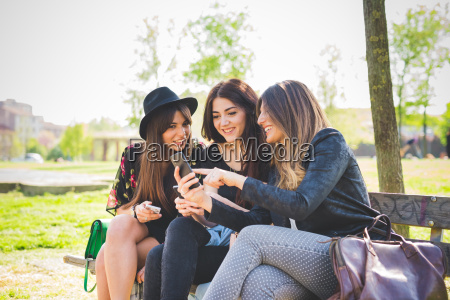 three young female friends reading smartphone