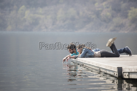 young couple lying on pier dipping