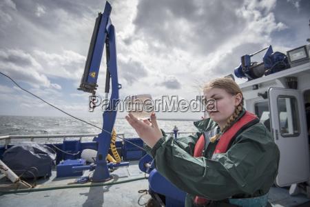 female scientist inspecting sample of plankton