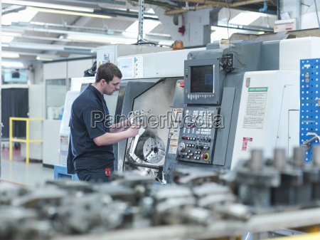 male worker inspecting parts on cnc