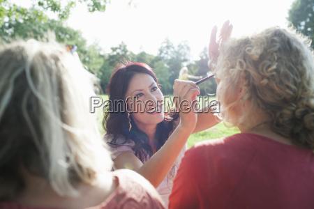 female adult friends applying make up