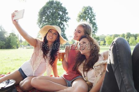 female friends taking smartphone selfie at