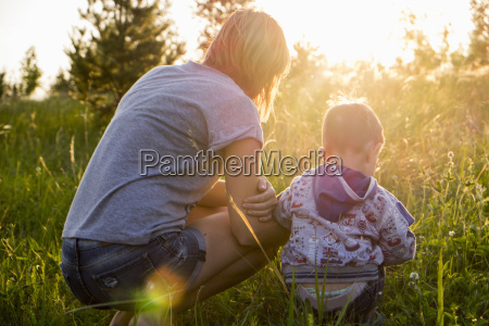 mother and son crouching in field