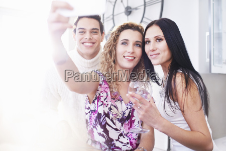 three young adult friends posing for
