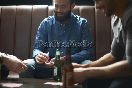 three male friends playing cards in