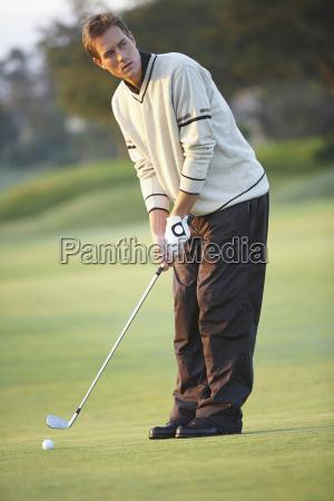 golfer holding golf club preparing to