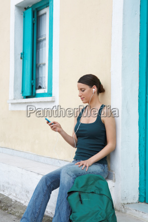young woman sitting outside greek house