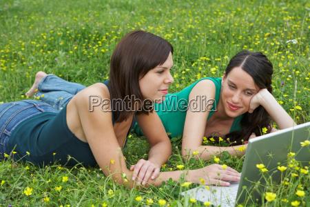 two young women lying in meadow