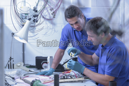 two male workers assembling electronics in