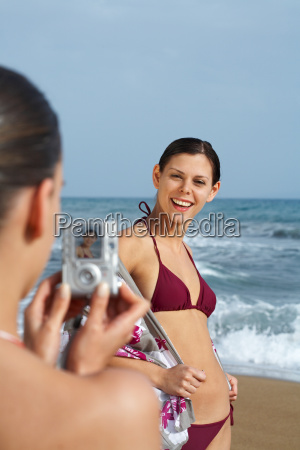 two young women on beach taking