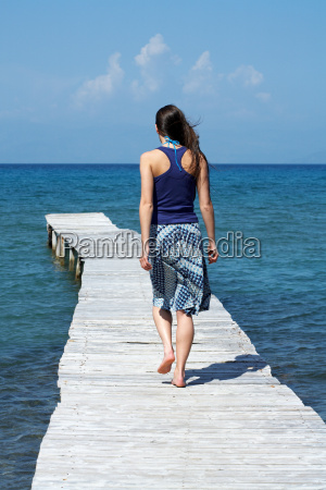 young woman walking on dock