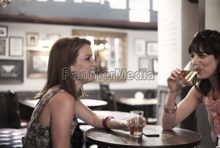 two female adult friends drinking beer
