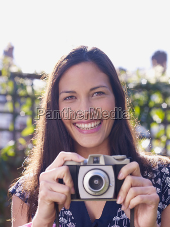 young woman smiling and holding camera