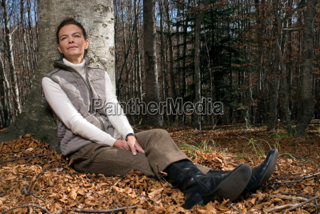 woman leaning against a tree smiling